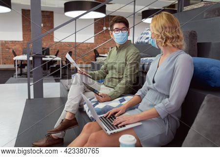 Male and female colleague in face masks sitting in foyer discussing and using tablet and laptop. working in business at a modern office during coronavirus covid 19 pandemic.