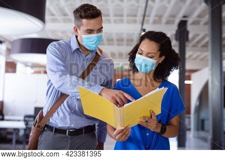 Diverse male and female colleague in face masks discussing paperwork in office corridor. working in business at a modern office during coronavirus covid 19 pandemic.