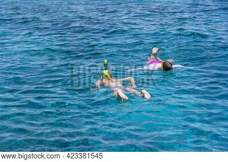 Young Girls Snorkeling In Blue Clear Waters Above Coral Reef On Red Sea In Egypt. Travel And Lifesty