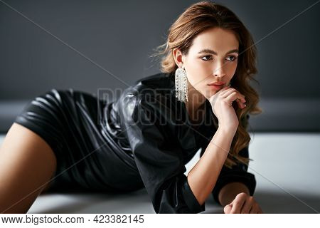 Trendy Sexy Young Woman In Black Cloth Posing Over Studio Background