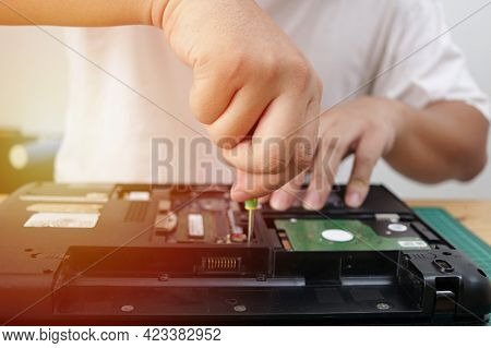 Close Up Of Technician Engineer Trying To Repairing Broken Laptop. Computer Repairs And Upgrade Conc