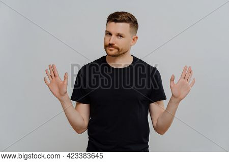 Saying No. Young Bearded Man In Black Tshirt Demonstrating Refusal Sign Or Stop Gesture, Asking Not