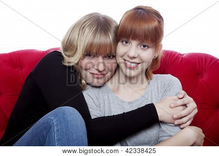 Young Beautiful Blond And Red Haired Girls Hug While Sitting On Red Sofa In Front Of White Backgroun