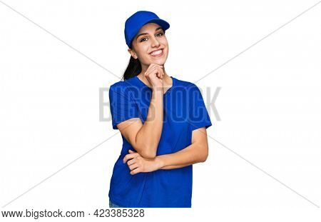 Young hispanic girl wearing delivery courier uniform looking confident at the camera with smile with crossed arms and hand raised on chin. thinking positive.