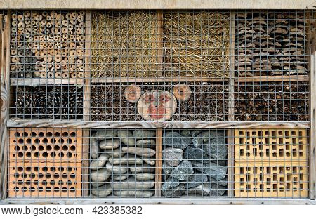 House For Insects. A Box Made Of Bark, Straw And Stones. Bricks, Cones And Bamboo For The Insect To