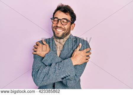 Handsome man with beard wearing business jacket and glasses hugging oneself happy and positive, smiling confident. self love and self care