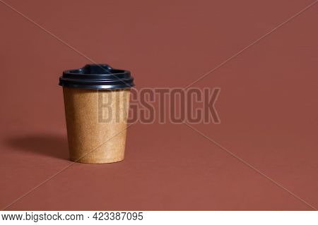 Disposable Coffee Cup For Cafe On Brown Background. Brown Cardboard Mockup Of Eco Coffee Cup With Pl
