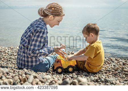 Mom And Little Child On The Stony Coast Of The Sea Are Playing Together And Collecting Stones. Conce