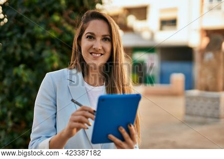 Young blonde businesswoman working using touchpad at the city.