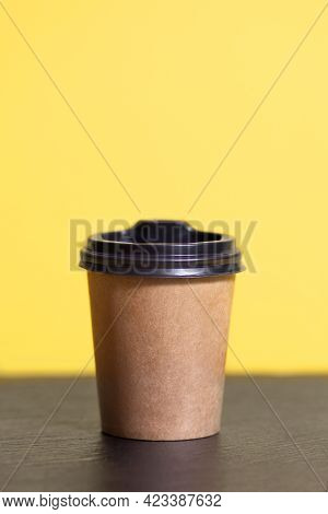 Disposable Coffee Cup For A Cafe On A Yellow Background. Brown Cardboard Mockup Of An Eco-friendly C