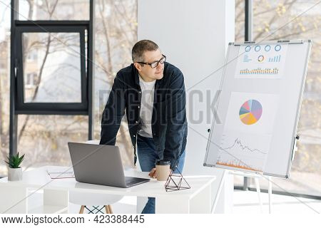 A Man, Strong Physique, Dressed In Casual Clothes Works In The Office