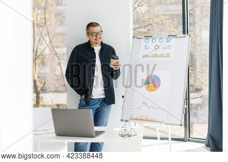 A Man Dressed In Casual Clothes Working In The Office, Standing Near A Table With A Laptop