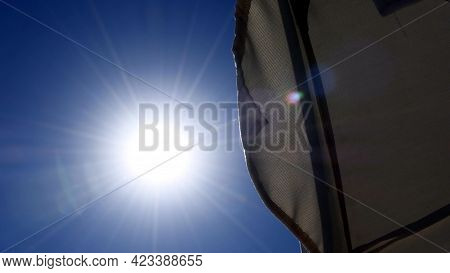 Sun Shines In Blue Sky With Star Shaped Sunbeams And Sun Flares On Textile Tent. View From Under Sun