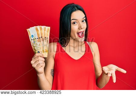 Young hispanic girl holding 500 philippine peso banknotes celebrating achievement with happy smile and winner expression with raised hand