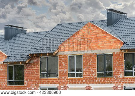Frame Duplex Townhouse Under Construction With Metal Roof And Chimney Pipe.