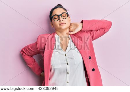 Beautiful middle eastern woman wearing business jacket and glasses suffering of neck ache injury, touching neck with hand, muscular pain