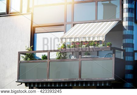 Beautiful Apartment Building Balcony With Sushade Protection Awning, Multiple Flowers In Jardinieres