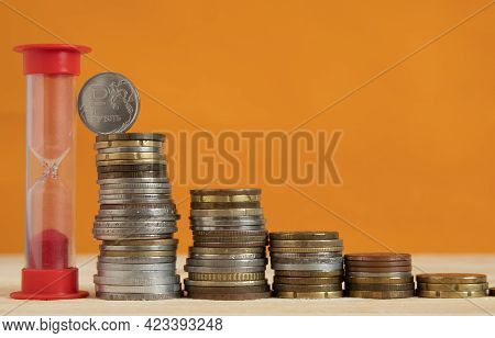 An Hourglass And A Pyramid Of Stacks Of Coins. The Ruble Coin Is At The Top. The Concept Of Strength