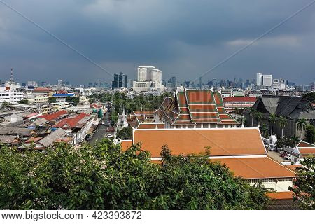 Bangkok Urban Area. Old And Modern, New And Decrepit Buildings Nearby. Skyscrapers Against A Cloudy