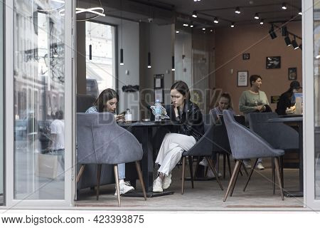 Moscow, Russia - 09 June 2021, Two Young Girls Are Drinking Coffee In A Cafe With An Open Veranda.