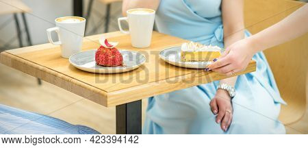 The Waitresss Hand Puts The Piece Of Cupcake On The Table At A Cafe, Woman Hand Is Putting Round Lit