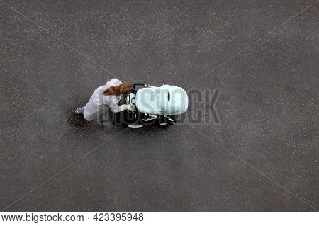 Woman With A Baby Stroller Crossing Wet Road, Top View. Concept Of Motherhood, Single Mom With Pram