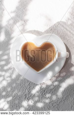 A Cup Of Cappuccino On A Saucer And Shade From The Sun. Coffee Drink. Copy Space. A Heart-shaped Cup