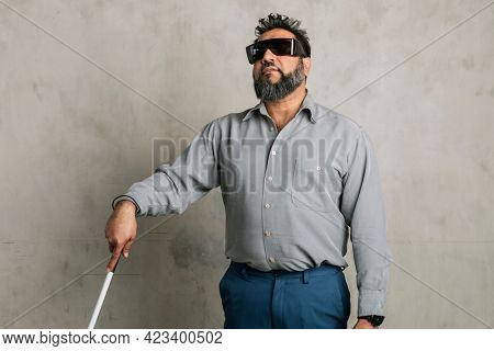 Blind Indian man wearing black goggles and using a white cane