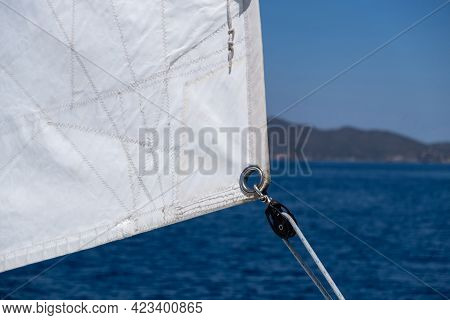 Sail Detail, Eyelet And Rope Closeup View. Blur Land And Sea Background
