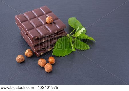Chocolate Bars With Hazelnuts, Next To Mint And Hazelnuts, On A Black Background