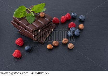 Chocolate Bars With Hazelnuts, Near Blueberries And Raspberries And The Hazelnut Itself, On A Black