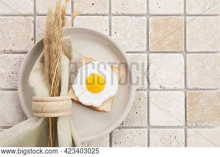 Stylish Serving On A Travertine Mosaic Background. Linen Napkin And Egg On Plate. Top View