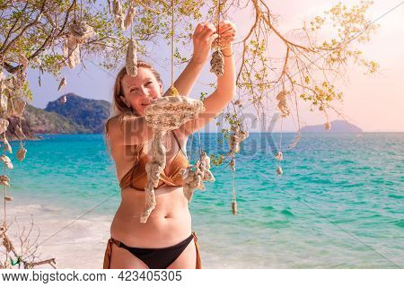 A Blonde Woman In A Bikini On The Seashore With Corals, Makes A Wish On A Sunny Day. Travel And Tour