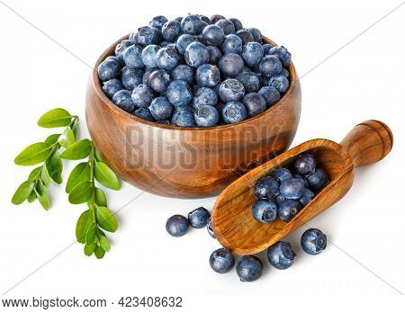 Berry blueberry in wooden plate with green leaf. Fruity still life. Healthy eating, isolated on white background.