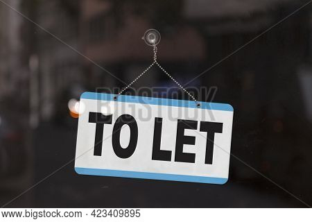 Close-up On A Sign In The Window Of A Shop Displaying The Message: To Let.