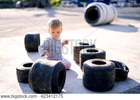 Child Is Kneeling On The Asphalt Surrounded By A Pile Of Small Car Tires