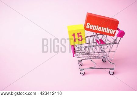 September 15th. Day 15 Of Month, Calendar Date. Close Up Toy Metal Shopping Cart With Red And Yellow