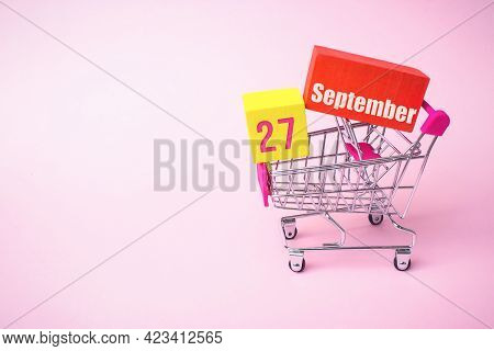 September 27th. Day 27 Of Month, Calendar Date. Close Up Toy Metal Shopping Cart With Red And Yellow