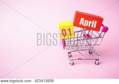 April 1st . Day 1 Of Month, Calendar Date. Close Up Toy Metal Shopping Cart With Red And Yellow Box