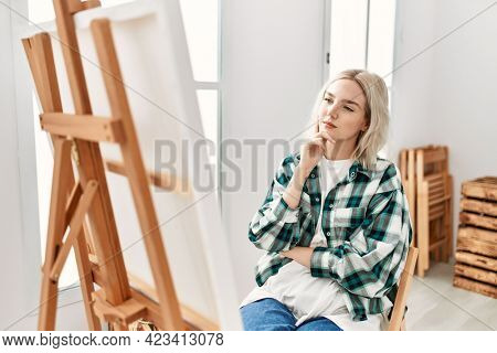 Young artist student girl concentrated looking canvas at art studio.