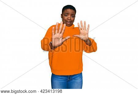 Young african american woman wearing casual clothes afraid and terrified with fear expression stop gesture with hands, shouting in shock. panic concept.