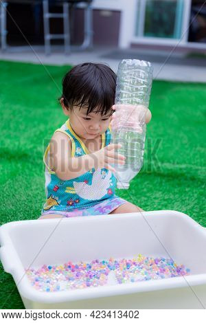 Vertical Image. Asian Baby Boy Playing Colorful Water Beads. Child Pouring Rainbow Beads From Bottle