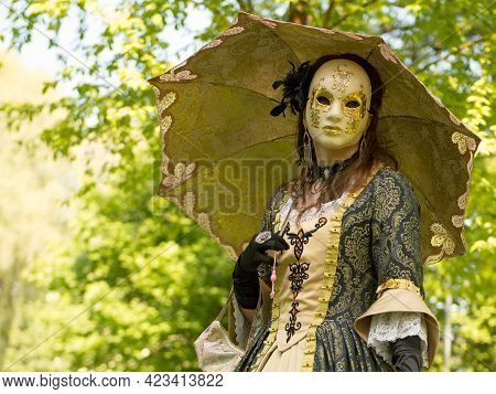 Costumed And Masked Woman At Venetian Carnival With Golden Umbrella. Blu Sky And Trees In The Backgr