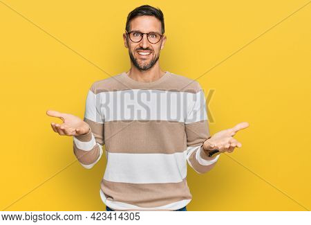 Handsome man with beard wearing casual clothes and glasses smiling cheerful with open arms as friendly welcome, positive and confident greetings