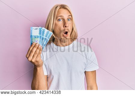 Caucasian young man with long hair holding 1000 hungarian forint banknotes scared and amazed with open mouth for surprise, disbelief face