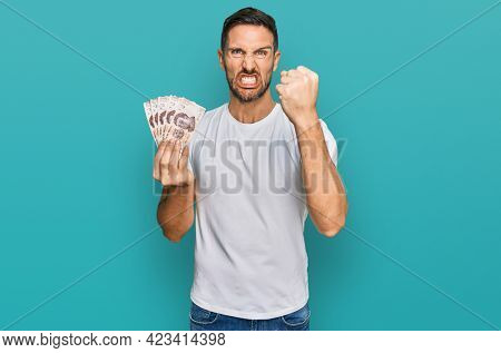 Handsome man with beard holding 50 mexican pesos banknotes annoyed and frustrated shouting with anger, yelling crazy with anger and hand raised