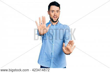 Hispanic man with beard wearing casual business shirt afraid and terrified with fear expression stop gesture with hands, shouting in shock. panic concept.