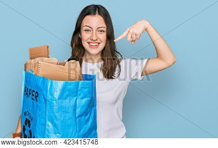 Young beautiful woman holding recycling wastebasket with paper and cardboard pointing finger to one self smiling happy and proud
