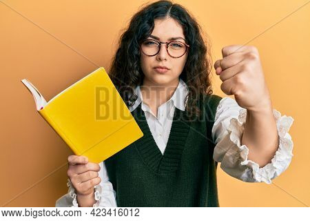 Young brunette woman with curly hair reading a book wearing glasses annoyed and frustrated shouting with anger, yelling crazy with anger and hand raised