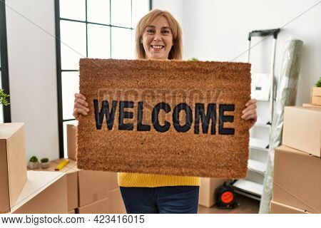 Middle age blonde woman smiling happy holding doormat at new home.